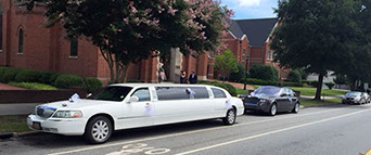 A stretch limousine waits outside the Catholic church in Greenville, SC, as a beautiful couple gets married on a gorgeous Saturday afternoon.