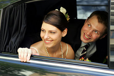 A couple celebrates their wedding day in Greenville, SC as their wedding party and guests cheer for them in their getaway limousine.